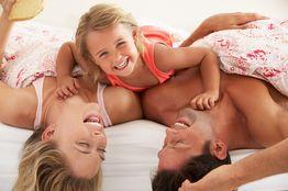 ALL IN Hotels Familie ausgelassen und glücklich im Bett