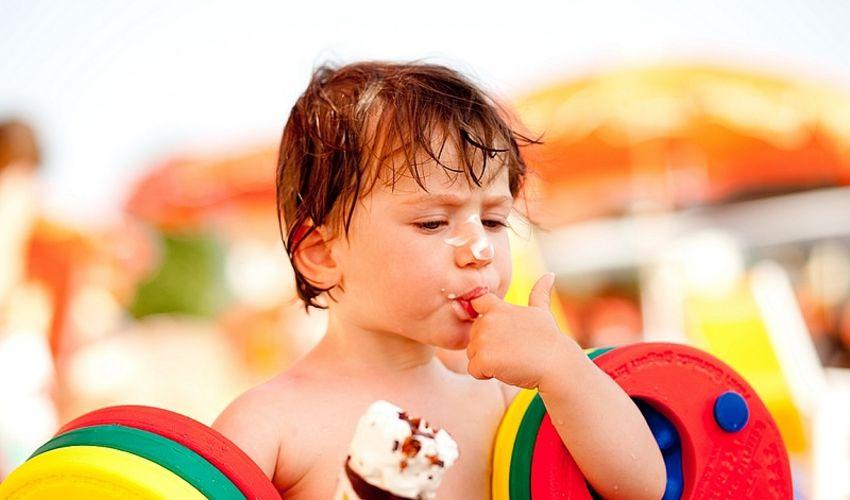 Kind mit Eis lustvoll den Finger schleckend.