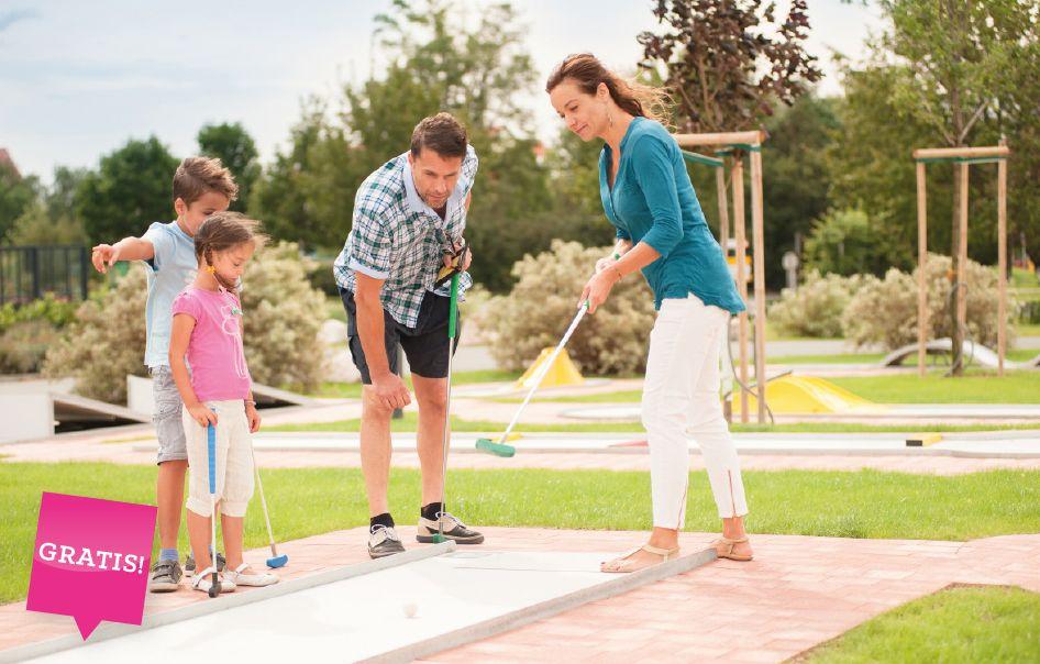 Mama Papa und Kinder beim Minigolf in der Natur