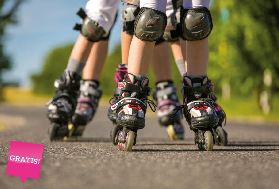 Kinder fahren mit kostenlosen Inlineskates in der Natur, auf der Strasse