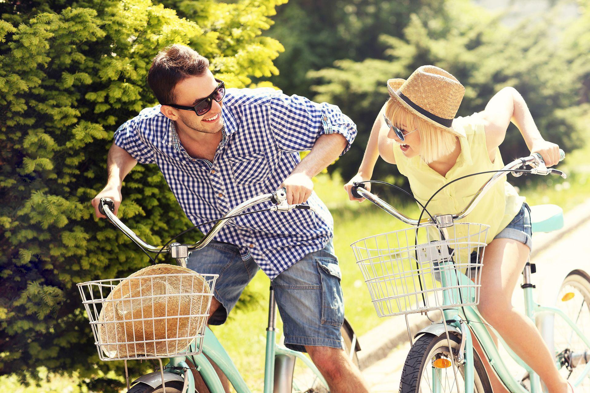ALL IN Hotels - Mann und Frau am Fahrrad stehen und genießen die wunderschöne Naturlandschaft
